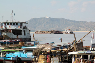 A barge with teak logs from northeastern Myanmar makes its way down the Irrawaddy River. The logs are mostly for export. Profits go to the government.