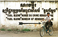 1997: A boy cycles past a sign for the Tuol Sleng genocide museum, a former Phnom Penh high school which the Khmer Rouge turned into an interrogation and torture center during their 1975-79 reign. Photo: AFP/Emmanuel Dunand