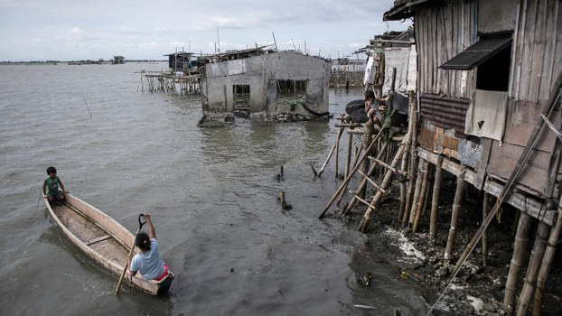 Residents using a boat to travel across the water in Bulacan, a region in the Philippines that has sunk 1.5-2.4 inches a year since 2003.