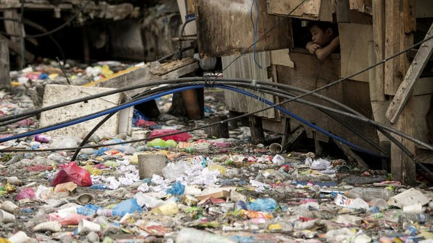 A boy looks out from a window of a house beside a garbage-filled creek that flows between the makeshift homes of a slum in Manila, capital of the Philippines, May 12, 2018.