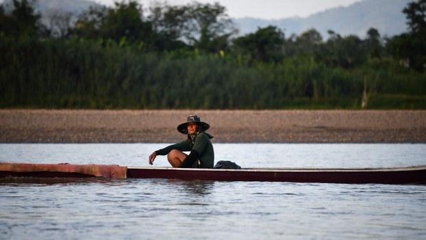 A fisherman navigates the Mekong River between Thailand and Laos, Sept. 20, 2019.