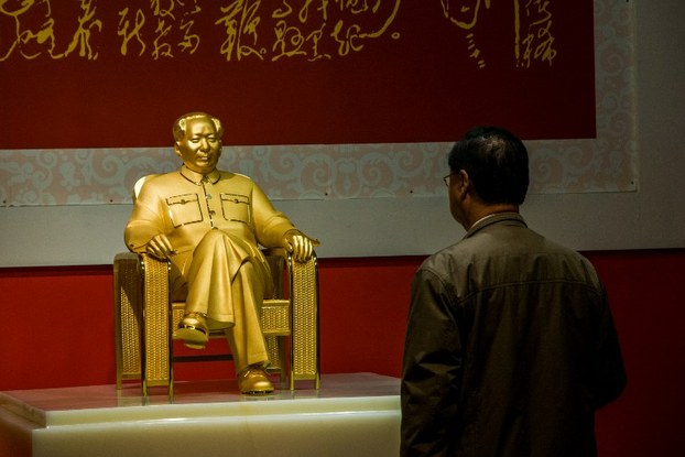 A visitor looks at a gold and jade statue of Mao Zedong to commemorate his 120th anniversary displayed in Guangdong province, Dec. 13, 2013.