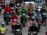 Motorists wearing face masks ride on a busy road in Hanoi, as Vietnam eased its nationwide social isolation effort to prevent the spread of the COVID-19 novel coronavirus, April 23, 2020.