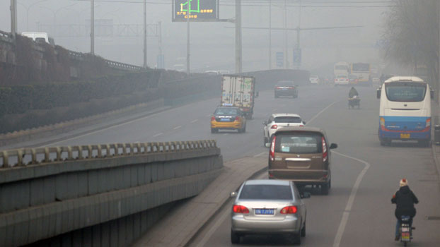 Cars drive along a road on a polluted day in China's capital Beijing, Dec. 25, 2015.