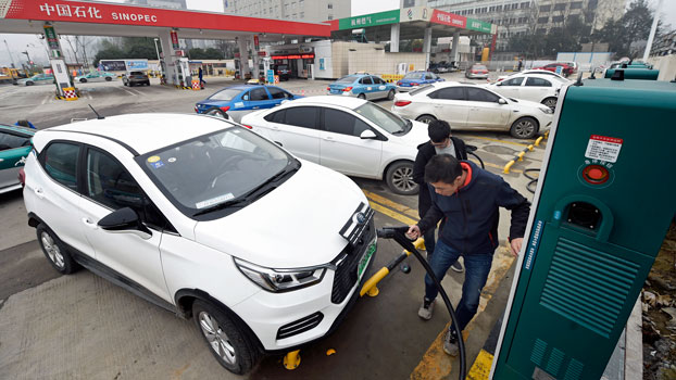 A driver plugs an electric vehicle into a charging station at a Sinopec service station in Hangzhou, eastern China's Zhejiang province, Jan. 14, 2019.