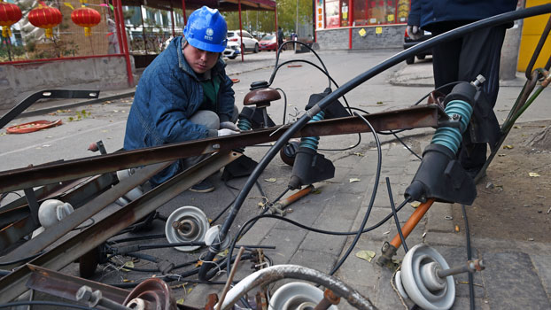 A worker takes apart electrical equipment after upgrading overhead power cables on a street in Beijing, Nov. 17, 2015.