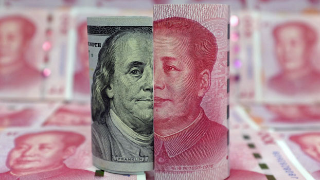 A Benjamin Franklin US 100-dollar banknote and a Chinese 100-yuan banknote depicting late Chinese chairman Mao Zedong are seen in a photo illustration, Jan. 21, 2016.