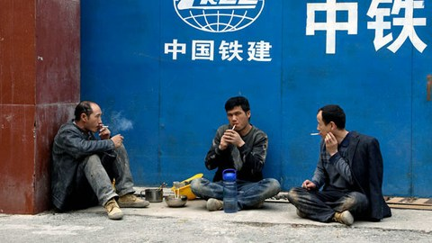 Workers smoke after lunch outside a construction site for the China Railway Construction Corporation in Beijing, China, March 20, 2019. The state-owned enterprise is one of the world's largest construction firms handling both domestic projects and China's overseas ventures.