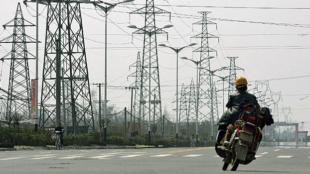 A motorbike rider passes electricity pylons alongside a roadway on the outskirts of Chengdu, capital of southwestern China's Sichuan province, in a file photo.