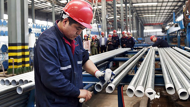 A worker checks steel pipes at a factory in Zouping, eastern China's Shandong province, April 17, 2018.