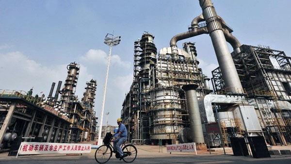 A worker rides a bicycle at a Sinopec oil refinery in Wuhan, central China's Hubei province, in a file photo. Credit: