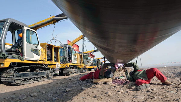 Chinese workers weld pipes at the construction site of the second project of west-to-east natural gas transmission pipeline in Fengle town of Wuwei city, northwestern China's Gansu Province, in a file photo.