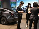 People wearing face masks are seen in a Tesla shop in Wuhan in China's central Hubei province, April 18, 2020.