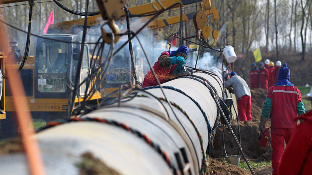 Workers lay pipelines for China National Petroleum Corp.'s Shaanxi-Beijing natural gas pipeline network ahead of Beijing's winter heating season, in Xianghe, northern China's Hebei province, Nov. 11, 2018.