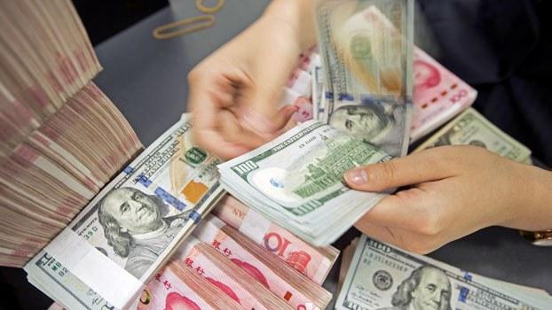 A Chinese bank employee counts 100-yuan notes and US 100-dollar bills at a bank counter in Nantong, eastern China's Jiangsu province, Aug. 6, 2019.