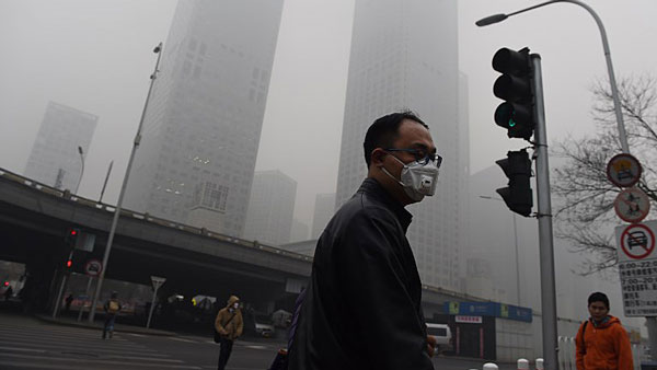 A Chinese pedestrian wears a face mask on a heavily polluted day in China's capital Beijing, Dec. 22, 2015.