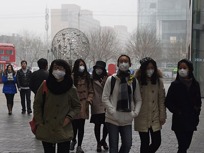 Chinese women wear face masks on a heavily polluted day in China's capital Beijing, Dec. 26, 2015.
