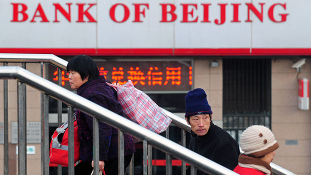 Pedestrians walk past a branch of the Bank of Beijing in China's capital Beijing in a file photo.
