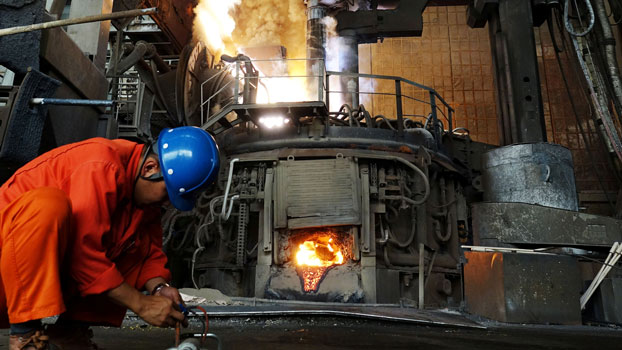 A man works in front of a furnace at a steel plant of the Dalian Special Steel Company Ltd. in Dalian, northeastern China's Liaoning province, June 20, 2018.