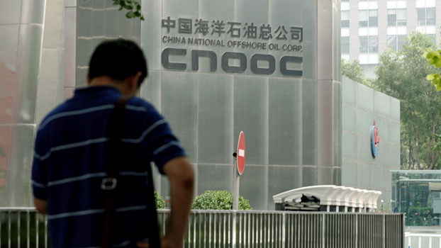 A man stands outside the headquarters building of China National Offshore Oil Corporation (CNOOC) in China's capital Beijing, July 29, 2016.