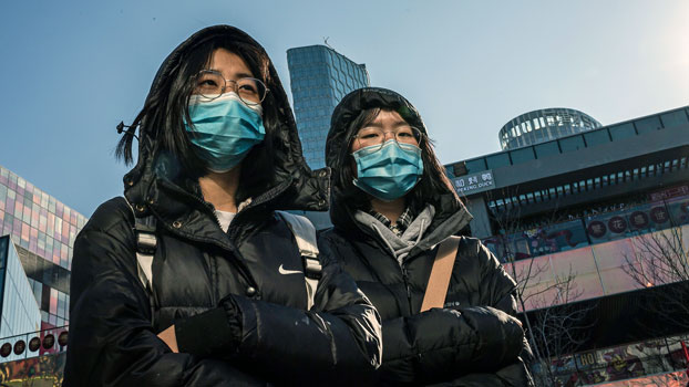 Two women wear protective masks as they walk outside a shopping mall in China's capital Beijing, Jan. 23, 2020.