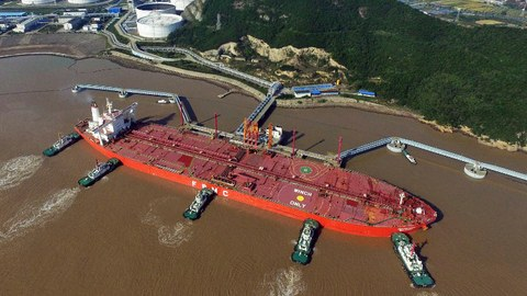 Tugboats dock an oil tanker on a crude oil quay at a port in Zhoushan, eastern China's Zhejiang province, Nov. 11, 2016.