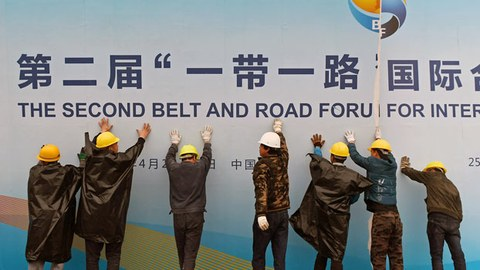 Chinese workers take down a Belt and Road Forum panel outside the venue of the forum in Beijing, April 27, 2019.
