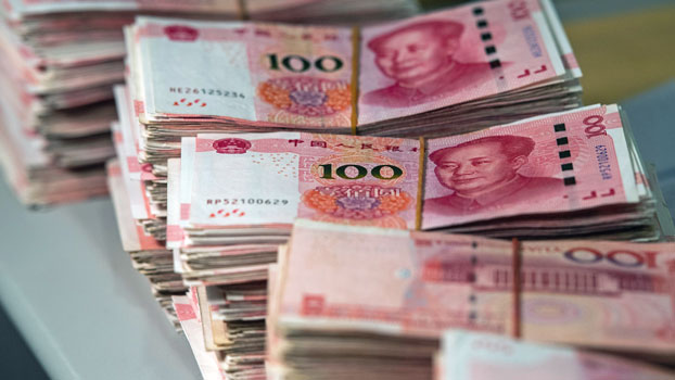 Bundles of 100-yuan notes sit on a desk at a bank in Shanghai, China, Aug. 8, 2018.