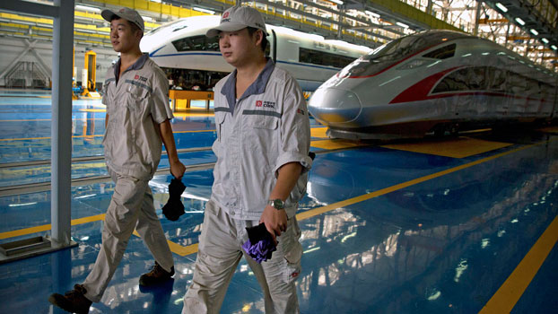 Chinese workers walk past parked high-speed trains at a maintenance yard in Beijing, Aug. 30, 2018.