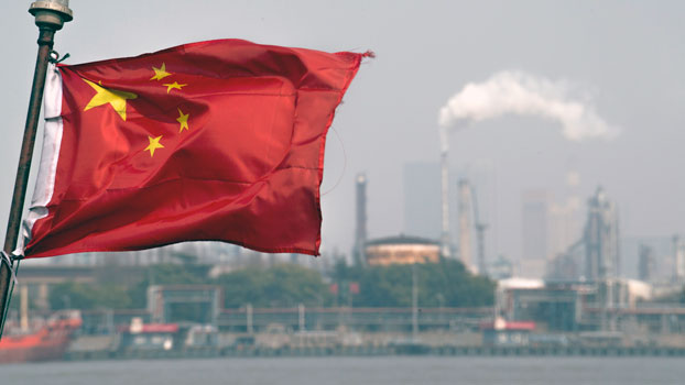 A Chinese flag flutters in front of the Shanghai Gaoqiao Company Refinery in Shanghai, March 22, 2018.