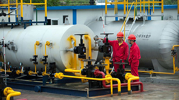 Workers examine drilling facilities in the Fuling work zone at a branch company of Sinopec, China's largest oil refiner, in southwestern China's Chongqing, Apr. 21, 2014.