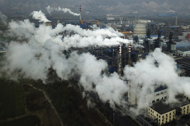 In this Nov. 28, 2019 file photo, smoke and steam rise from a coal processing plant in Hejin in central China's Shanxi Province.