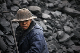 A worker piles coal in Huaibei, in eastern China's Anhui province, Feb. 7, 2010.