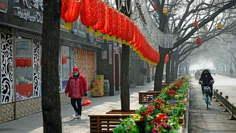 A woman walks past Chinese Lunar New Year decorations and shuttered bars in a retail district in Beijing, Feb. 11, 2020.