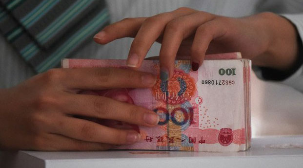 A post office employee in Beijing counts Chinese yuan in a file photo.