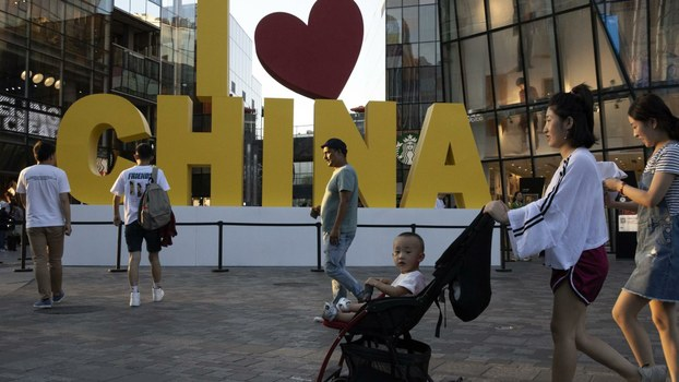 In this photo taken Monday, Sept. 23, 2019, shoppers visit a popular retail center in Beijing.