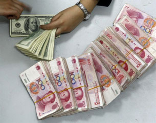 A Chinese bank worker arranges U.S. currency next to stacks of 100-yuan notes, March 20, 2010.