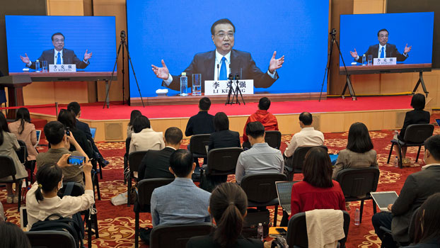 Chinese Premier Li Keqiang is seen on a screen as he speaks during a press conference via video conference at the end of the National People's Congress in Beijing, May 28, 2020.