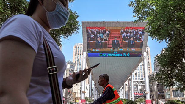A woman wearing a protective face mask walks near an outdoor screen of a news report about  Chinese President Xi Jinping attending the closing ceremony of the National People's Congress in Beijing, May 28, 2020.