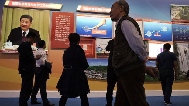 Visitors walk past a chart showing China's soaring GDP since 2012 and an image of Chinese President Xi Jinping at an exhibition highlighting the country's achievements under Xi's leadership at the Beijing Exhibition Hall in Beijing, in a file photo.