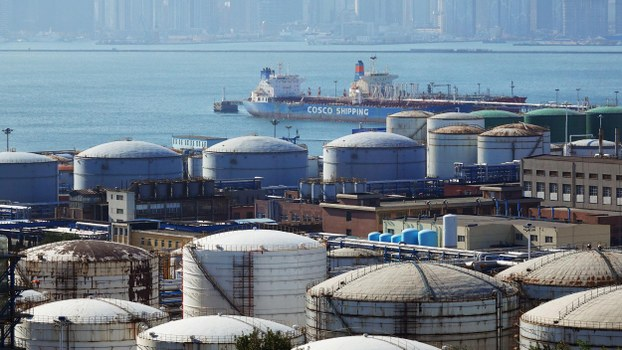 A China Ocean Shipping Company (COSCO) vessel is seen near oil tanks at the China National Petroleum Corporation (CNPC)'s Dalian Petrochemical Corp in Dalian, Liaoning province, China October 15, 2019. REUTERS