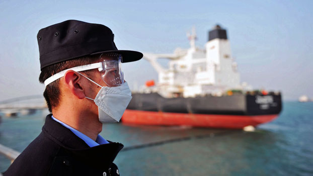 A police officer wearing a face mask amid concerns over the coronavirus keeps watch as a Kuwaiti oil tanker unloads crude oil at the port in Qingdao, eastern China's Shandong province, March 20, 2020.