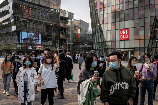 People wearing facemasks amid concerns over the COVID-19 coronavirus walk past a Uniqlo (R) and Adidas (L) retail store at a shopping mall in Beijing on April 19, 2020.