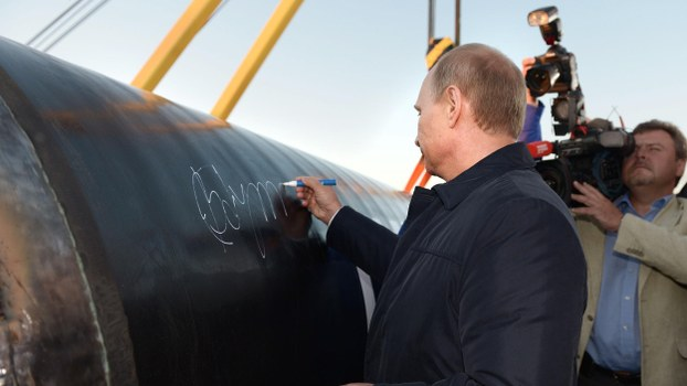 "Russian President Vladimir Putin, left, signs a pipe during the ceremony marking the construction of gas pipeline "" Power of Siberia"" connecting Russia and China near the village of Us Khatyn in Yakutsk region, Russia, Monday, Sept. 1, 2014."
