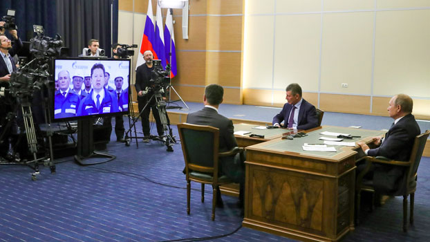 Russian President Vladimir Putin (R), Deputy Prime Minister of Russia Dmitry Kozak (2nd R), and Russian Minister of Energy Alexander Novak (back to a camera) attend a joint videoconference with Chinese President Xi Jinping during the inauguration of the Power of Siberia pipeline, at the Bocharov Ruchei residence in Sochi, Russia, Dec. 2, 2019.