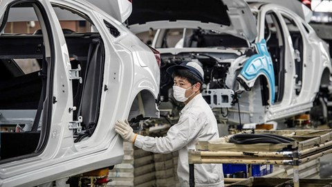 A Chinese employee wears a face mask as he works on an assembly line at the Dongfeng Honda auto plant in Wuhan, central China's Hubei province, March 23, 2020.