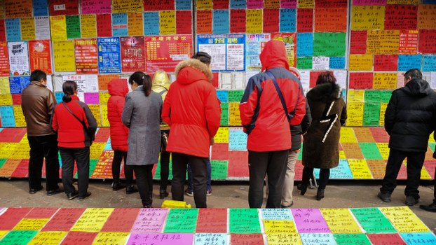 Job seekers look at employment postings at a recruitment fair in Qingdao, in eastern China's Shandong province, Feb. 20, 2019.