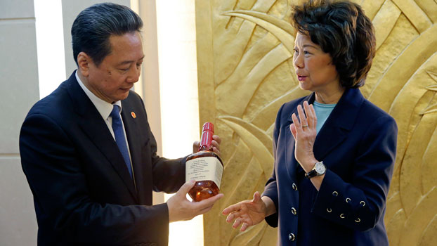 China's Transport Minister Li Xiaopeng (L) holds a bottle of whiskey given to him by US Secretary of Transportation Elaine Chao (R) after a signing ceremony at the Ministry of Transport in Beijing, April 27, 2018.