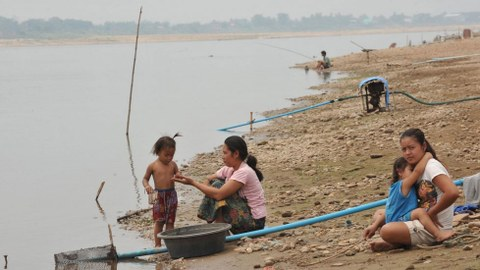Women and children sit on the bank of the drought-hit Mekong River nearthe Lao capital Vientiane, in file photo.