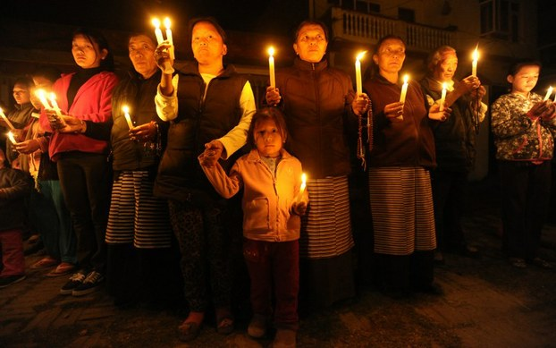 Tibetans-in-exile in Kathmandu, Nepal, take part in a candlelight vigil following a self-immolation attempt by a monk in Tibet, Feb. 13, 2013.